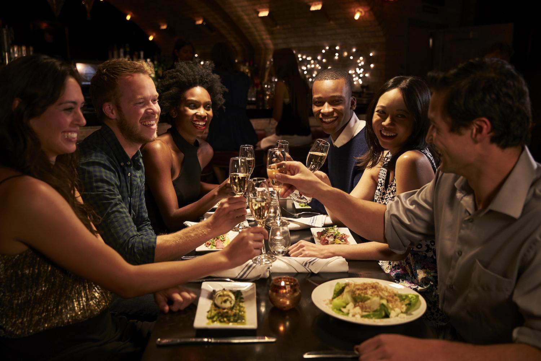 Seis personas compartiendo mesa en un restaurante y brindando con una copa de cava.