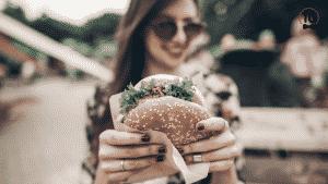 Mujer comiendo una hamburguesa.