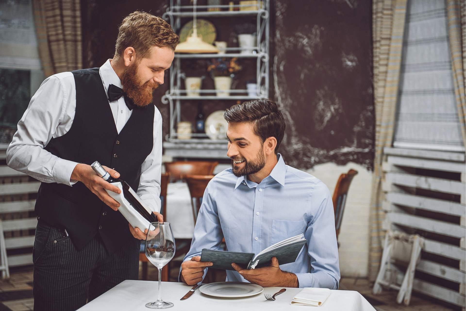 camarero-enseñando-botella-de-vino-a-cliente