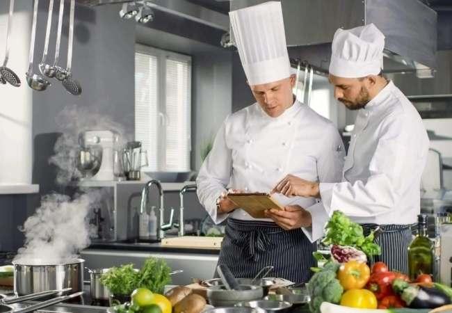 camareros viendo en una tablet en cocina de un restaurante los datos sobre que le pasa el programa tpv bar