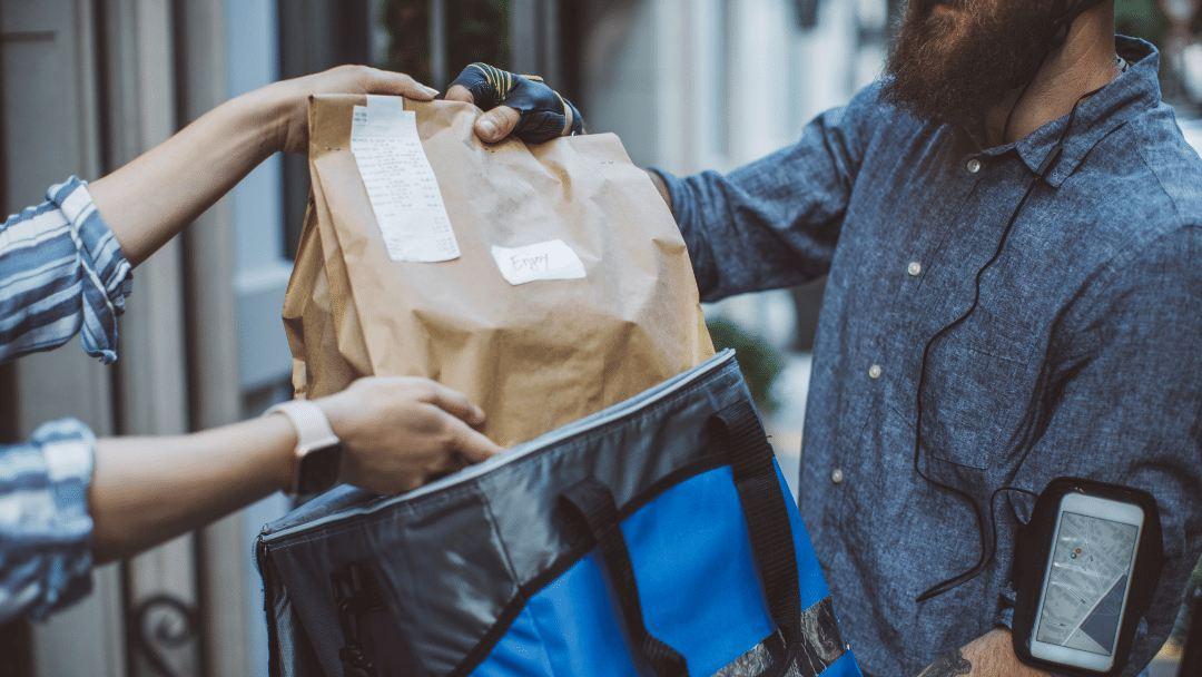 Imagen de un repartidor de delivery entregando al cliente su pedido