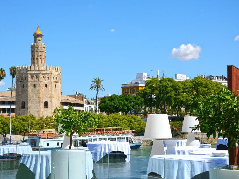 Imagen de la torre del oro desde la terraza de un restaurante en Sevilla.